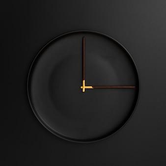 Assiette noire avec bâtons de chocolat en forme d'horloge