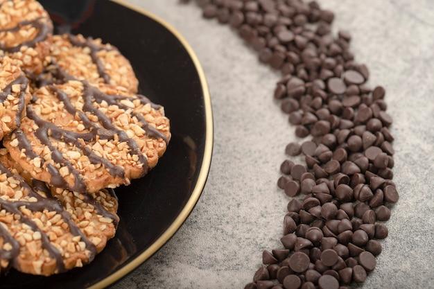 Assiette noire de biscuits à l'avoine et déposer le chocolat sur la table en pierre.