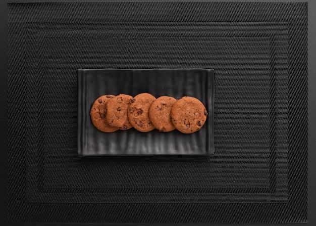 Assiette noire avec des biscuits sur un chiffon foncé