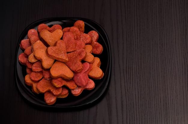 Assiette noire avec des biscuits rouges en forme de coeur sur une table noire, la saint-valentin. vue de dessus, surface
