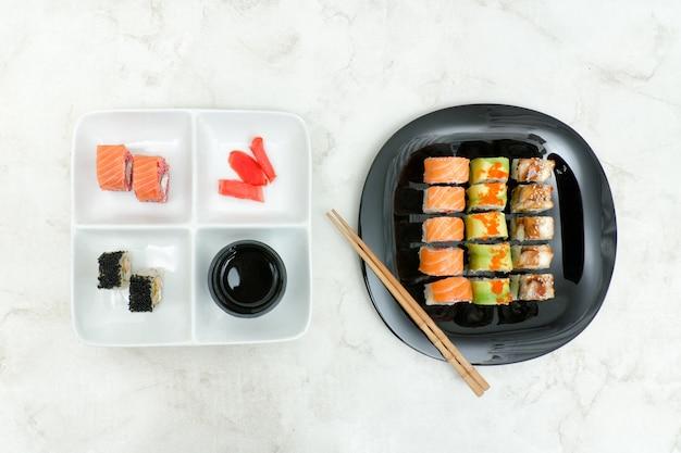 Assiette noire et blanche avec divers rouleaux et baguettes. vue de dessus