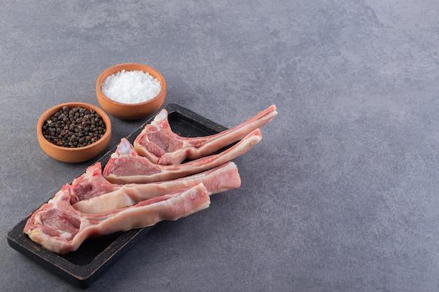 Assiette noire de côtelettes d'agneau crues sur table en pierre.