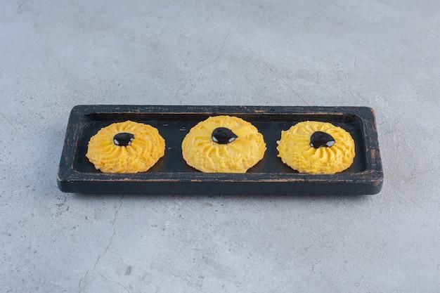 Une assiette noire de délicieux biscuits ronds sur fond de pierre.