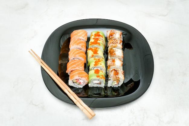 Assiette noire avec divers rouleaux et baguettes. vue de dessus