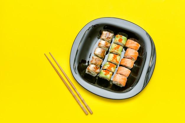 Assiette noire avec divers rouleaux sur jaune
