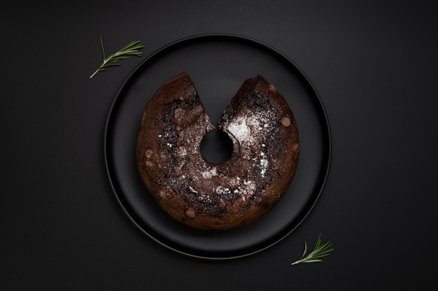 Assiette noire avec un gâteau au chocolat sur fond noir