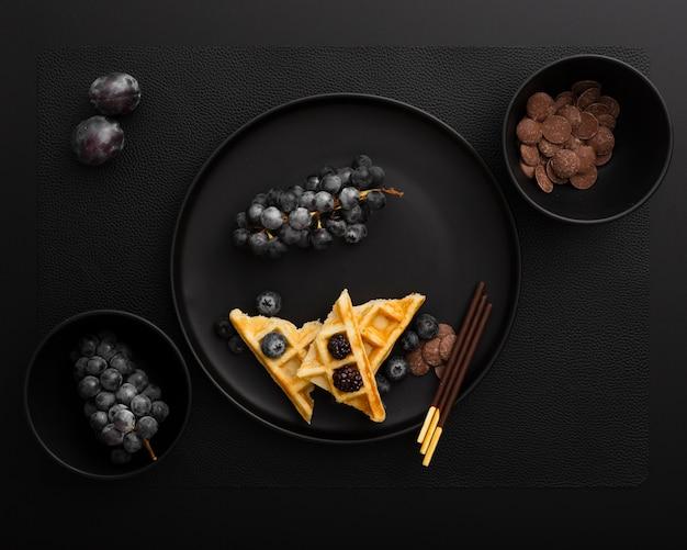 Assiette noire avec des gaufres et des raisins sur un fond sombre