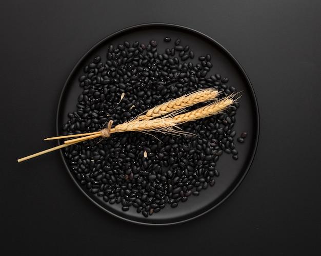 Assiette noire avec des haricots sur fond noir