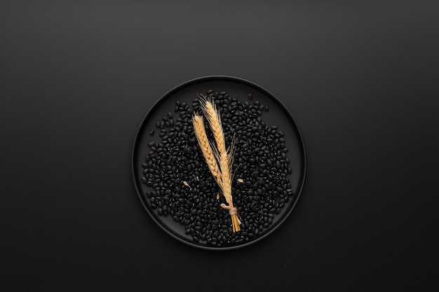 Assiette noire avec des haricots sur un fond sombre