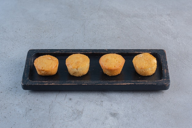Assiette noire de mini gâteaux sucrés sur pierre.
