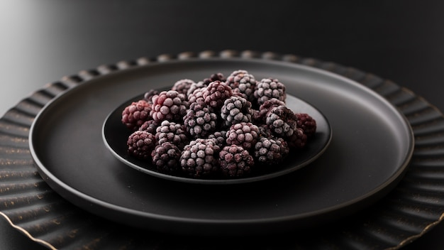 Assiette noire avec des mûres sur une table sombre