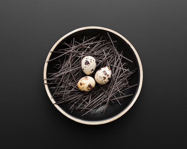 Assiette noire avec des oeufs sur un fond sombre