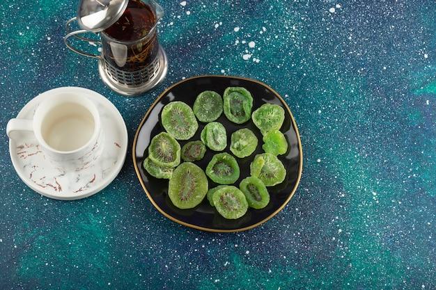 Une assiette noire pleine de kiwis séchés et une tasse de thé.