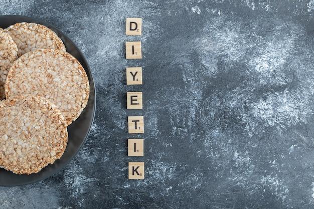 Une assiette noire pleine de pain de riz soufflé sur une surface en marbre.