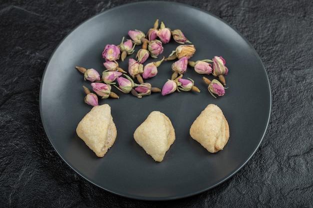 Une assiette noire pleine de roses séchées et de pâtisseries.