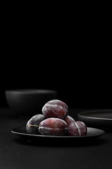 Assiette noire avec des prunes sur une table sombre