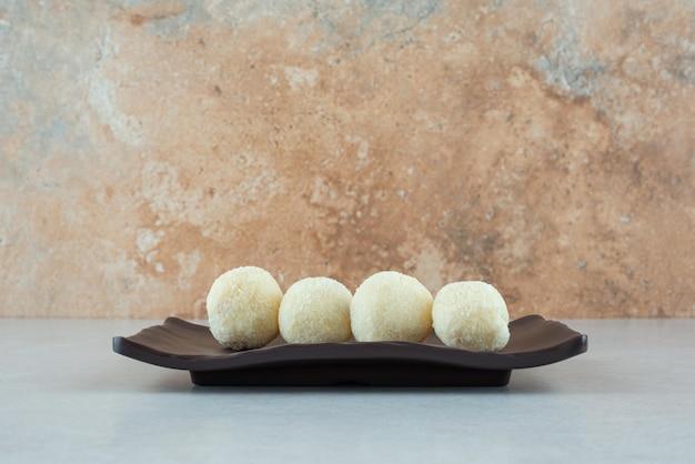 Une assiette noire avec quelques délicieux biscuits ronds.