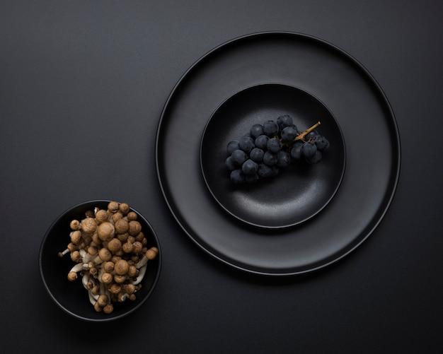 Assiette noire avec des raisins sur fond noir