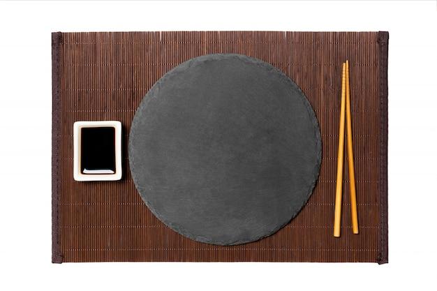 Assiette noire ronde vide avec des baguettes et de la sauce de soja, gingembre sur un tapis de bambou foncé