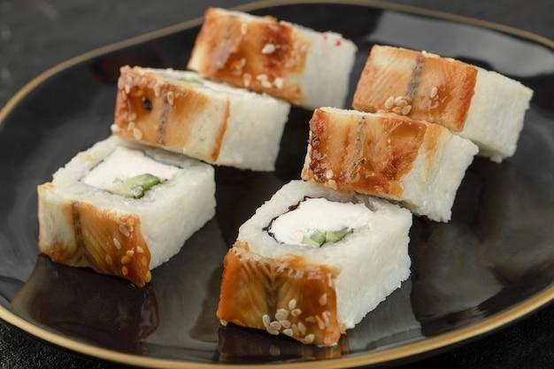 Assiette noire de rouleaux de sushi dragon avec anguille sur une surface noire