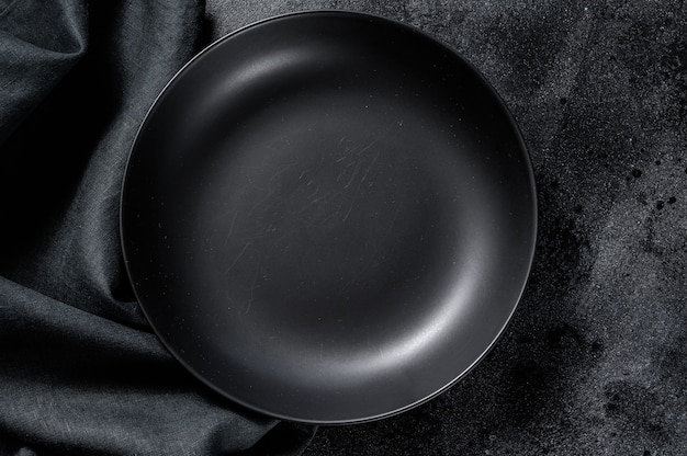 Assiette noire et une serviette sur fond noir. vue de dessus. espace copie