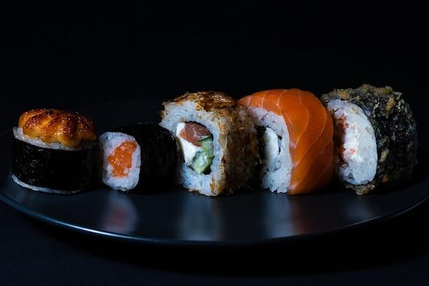 Sur une assiette noire, des sushis chauds, des makis cuits au four, des makis et des rouleaux de philadelphie