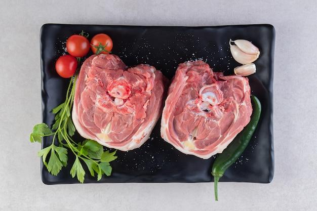 Assiette noire de viande d'agneau crue placée sur une table en pierre.