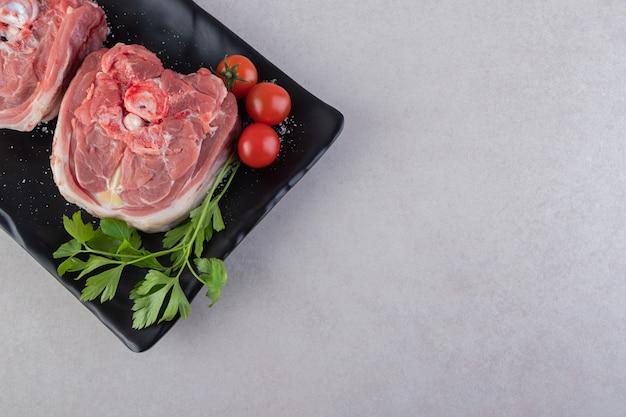 Assiette noire de viande crue aux tomates cerises sur table.