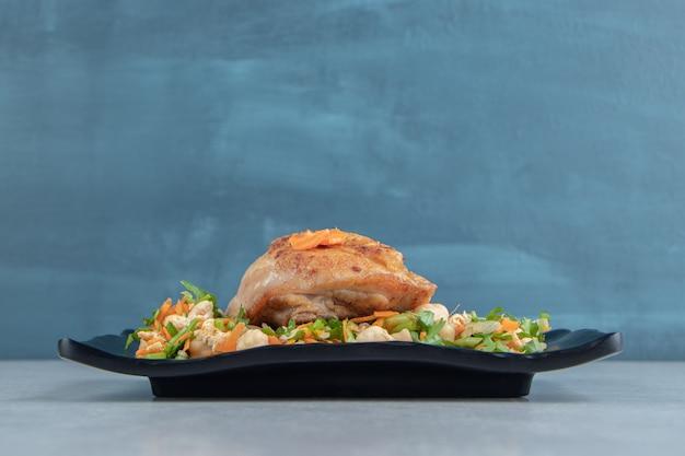Une assiette noire de viande frite au poulet et salade de légumes.