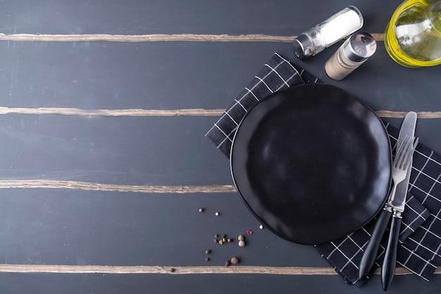 Assiette noire vide avec des épices.