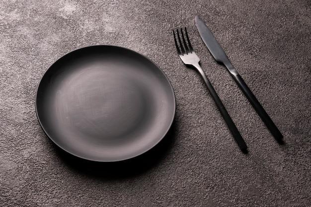Une assiette noire vide, une fourchette et une cuillère sur un fond sombre. nature morte minimaliste