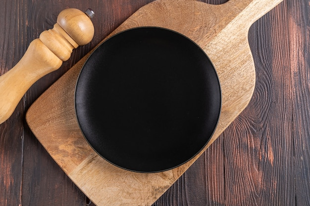 Assiette noire vide sur une planche à découper en bois, vue de dessus.