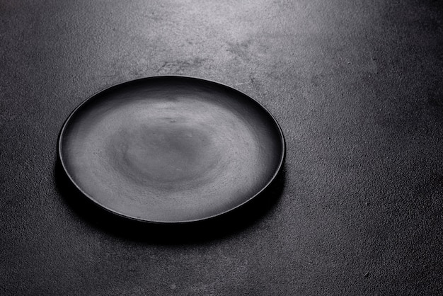 Assiette noire vide sur une table en pierre sombre