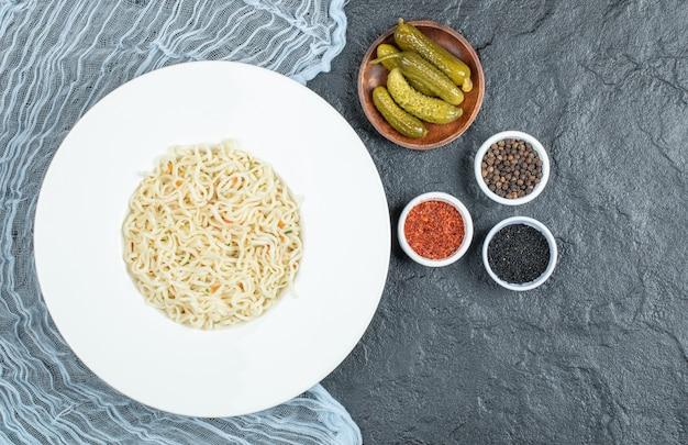 Assiette de nouilles, cornichons et épices sur une surface sombre.