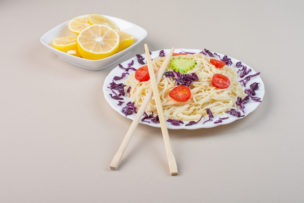 Une assiette de nouilles cuites avec des légumes et des tranches de citron frais.