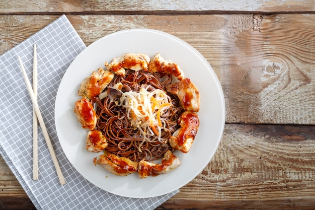 Assiette avec nouilles soba au sarrasin et légumes avec poulet et baguettes