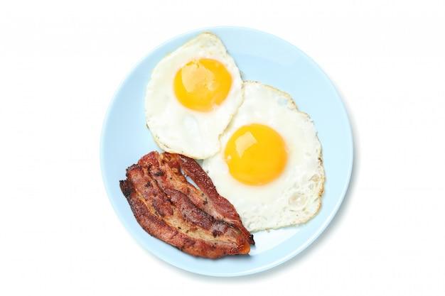 Assiette avec des œufs au plat et du bacon isolé