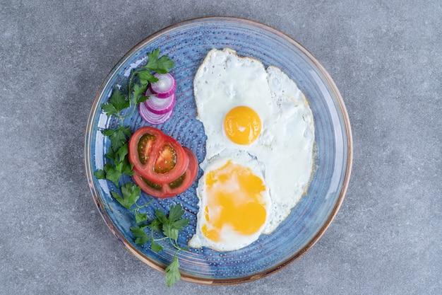 Une assiette avec des œufs au plat et des légumes tranchés. photo de haute qualité