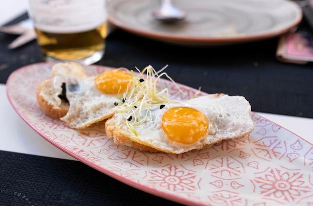 Assiette d'œufs au plat sur un mini pain grillé à la truffe