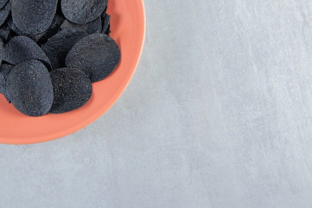 Assiette orange de chips noires croustillantes sur pierre.
