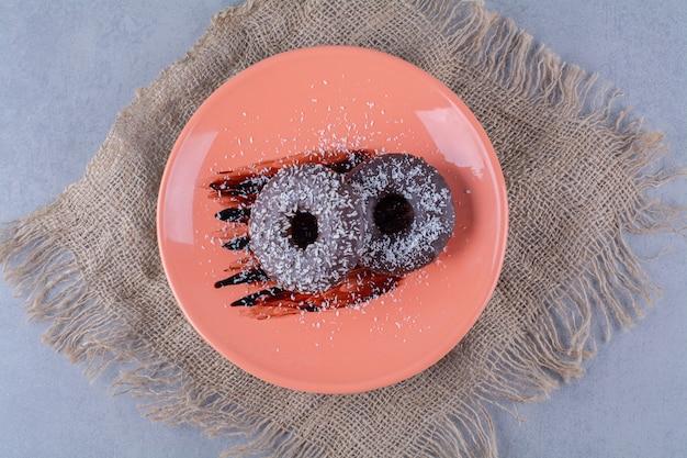 Une assiette orange de délicieux beignets au chocolat avec des pépites sur un sac