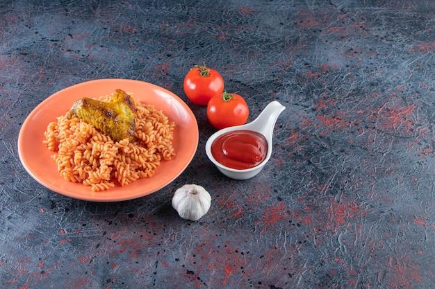 Assiette orange de pâtes fusilli avec aile de poulet sur une surface en marbre.