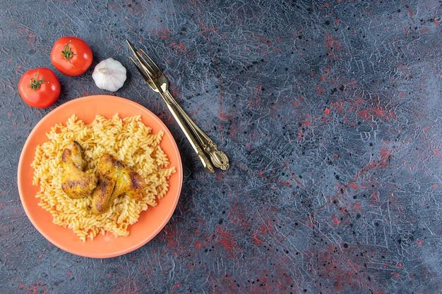 Assiette orange de pâtes fusilli avec ailes de poulet frites sur une surface en marbre.