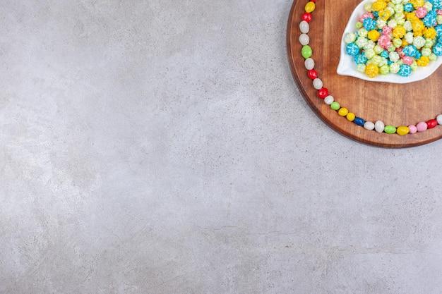 Une assiette ornée de bonbons entouré de bonbons sur planche de bois sur fond de marbre.