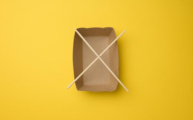 Assiette en papier brun vide et baguettes en bois sur fond jaune, vue de dessus. vaisselle jetable, zéro déchet