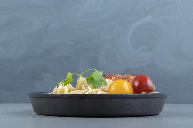 Assiette de pâtes et aile de poulet sur fond de pierre.
