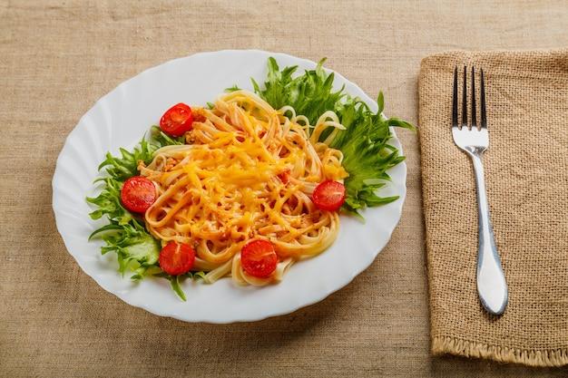 Une assiette de pâtes au fromage et aux tomates décorée d'herbes sur une table en bois à côté d'une serviette en lin et d'une fourchette. photo horizontale