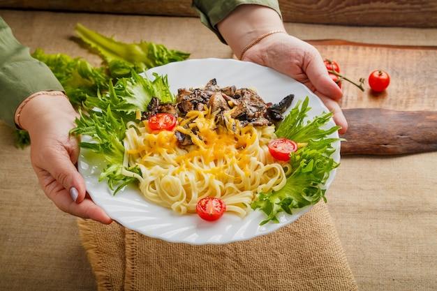 Une assiette de pâtes aux champignons et fromage dans les mains des femmes. photo horizontale
