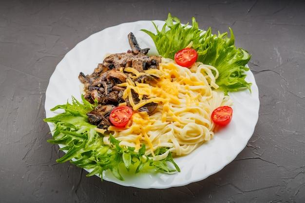 Une assiette de pâtes aux champignons et fromage garnie d'herbes sur un fond de béton gris. photo horizontale