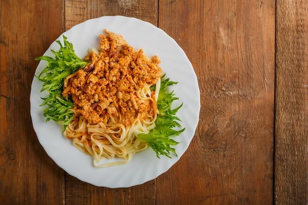 Une assiette de pâtes bolognaise décorée d'herbes sur une table en bois. photo horizontale